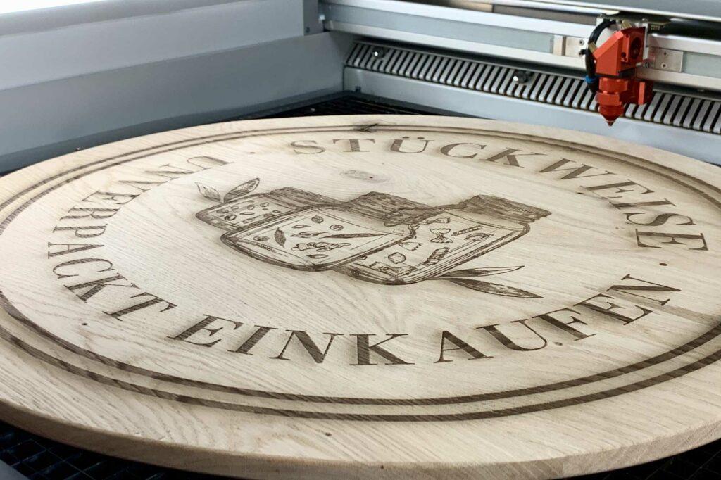 Lasergravur eines Logos und Text auf Holz